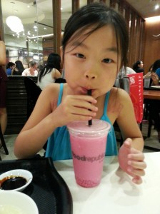 Keira is trying a yummy new drink in Singapore.