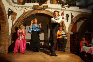 Flamenco dancing. The guy is dancing in this picture with his partner clapping in the background